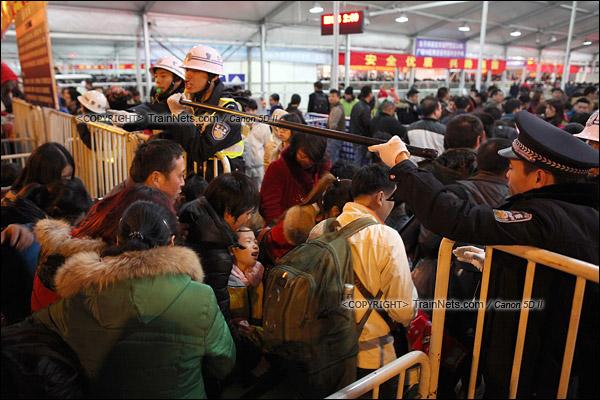 2016年2月1日。晚上10点,广州火车站广场。候车雨棚入口,警方打开栏杆分批放旅客进入候车雨棚。(IMG-9253-160201)