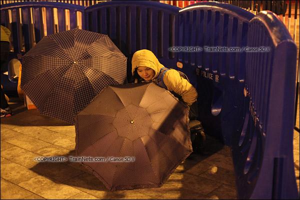 2016年2月1日。晚上10点,广州火车站广场。由于天气寒冷,不少乘客用雨伞遮挡寒风。(IMG-9322-160201)