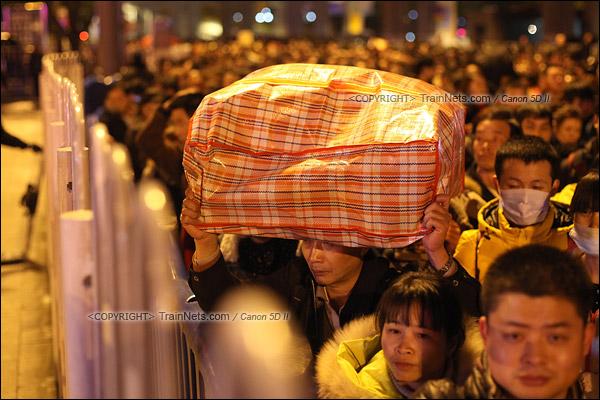 2016年2月1日。晚上11点,广州火车站。环市路被作为旅客安置点,警方在此设置关卡,分批放行排队进站的旅客。一位乘客头举行李,慢慢前行。(IMG-9343-160201)