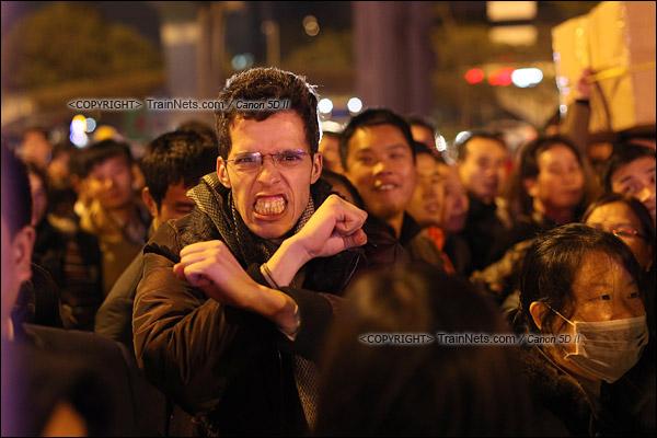2016年2月1日。晚上11点,广州火车站。环市路被作为旅客安置点,警方在此设置关卡,分批放行排队进站的旅客。一位前往郴州的外籍旅客,对镜头做着鬼脸。(IMG-9366-160201)