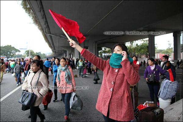 2016年2月2日。下午3点。广州火车站。环市路已经改为乘客疏散区。一名乘客举着地上捡到的红旗在空中挥舞,寻找人群中的同伴。(IMG-9388-160202)