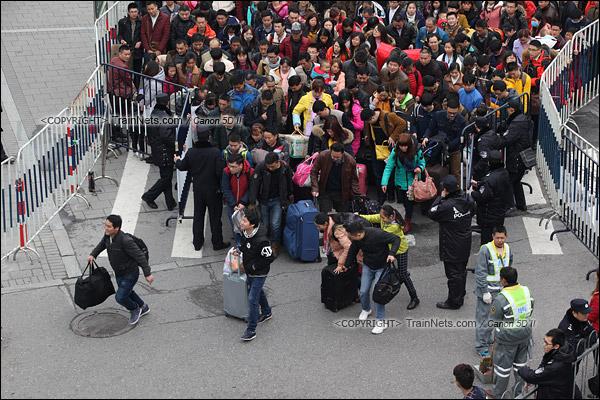 2016年2月2日。下午3点。广州火车站东广场。东广场进入环市路的一个分流闸口,闸口开放后,乘客纷纷小跑前行。(IMG-9520-160202)