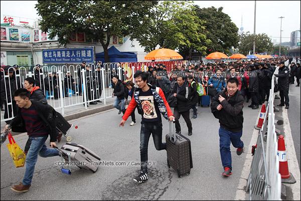 2016年2月2日。下午3点。广州火车站。环市路上警察筑起了分批放行闸口。闸口开放后,焦急的乘客纷纷往前跑。(IMG-9651-160202)