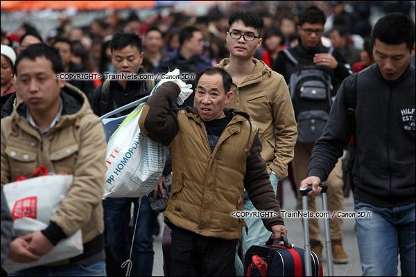 2016年2月2日。下午4点。广州火车站。环市路上警察筑起了分批放行闸口。闸口开放后,一名乘客走向下一道闸口。(IMG-9718-160202)