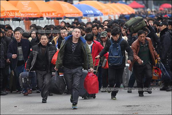 2016年2月2日。下午3点。广州火车站。环市路上警察筑起了分批放行闸口。闸口开放后,焦急的乘客纷纷往前跑。(IMG-9742-160202)