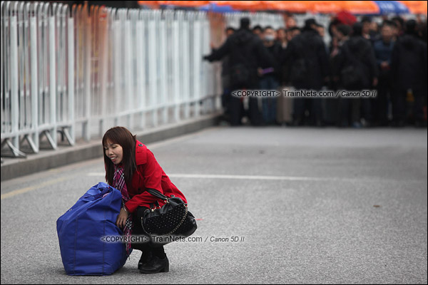 2016年2月2日。下午4点。广州火车站。环市路上警察筑起了分批放行闸口。闸口开放后,一名提着沉重行李的女士,蹲在地上休息。(IMG-9786-160202)