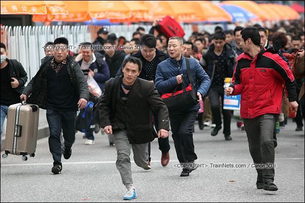 2016年2月2日。下午3点。广州火车站。环市路上警察筑起了分批放行闸口。闸口开放后,焦急的乘客纷纷往前跑。(IMG-9787-160202)