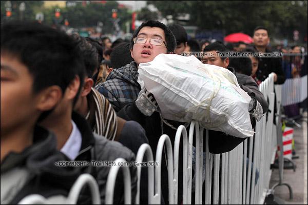 2016年2月2日。下午3点。广州火车站。环市路上警察筑起了分批放行闸口。一位乘客焦急地看着前方。(IMG-9878-160202)