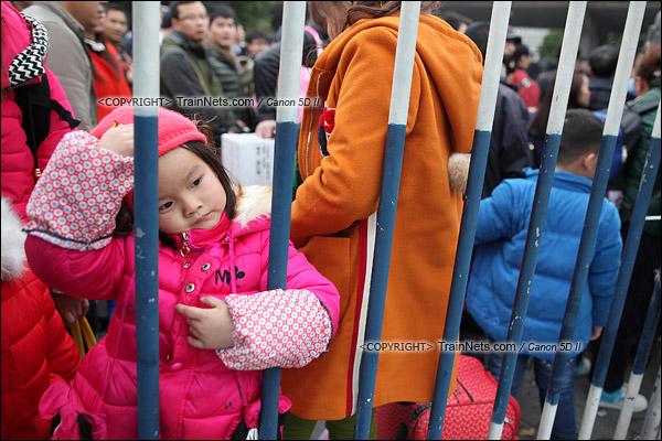 2016年2月2日。下午4点。广州火车站东广场。旅客正在通过绕圈排队进入候车。一位小女孩抱着栏杆发呆。(IMG-9911-160202)