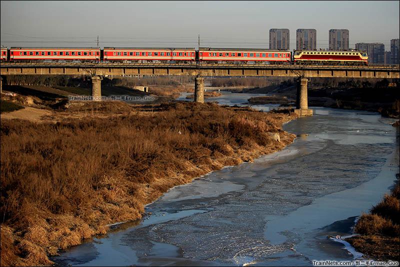 2016年1月25日。西安十里铺,原SS7C本务的K626次(西安-宜昌东)驶过冰封的浐河。(图/郭二毛Ermao_Guo)