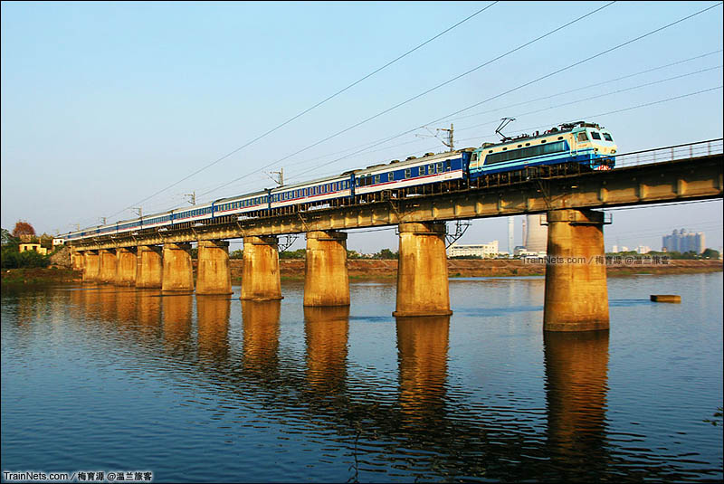 2014年11月26日。浙江金华。沪昆线。SS8牵引全蓝25K车厢的T211次(上海南-深圳)列车驶过金华江。(图/梅育源 @温兰旅客)