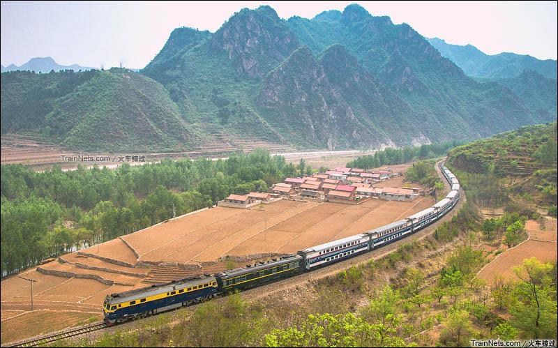 2016年5月1日。河北省鹰手营子,京承线上,客车K7711次(北京-承德)穿过村庄,即将穿越京承线最长隧道-夹马石隧道。(图/火车掠过)