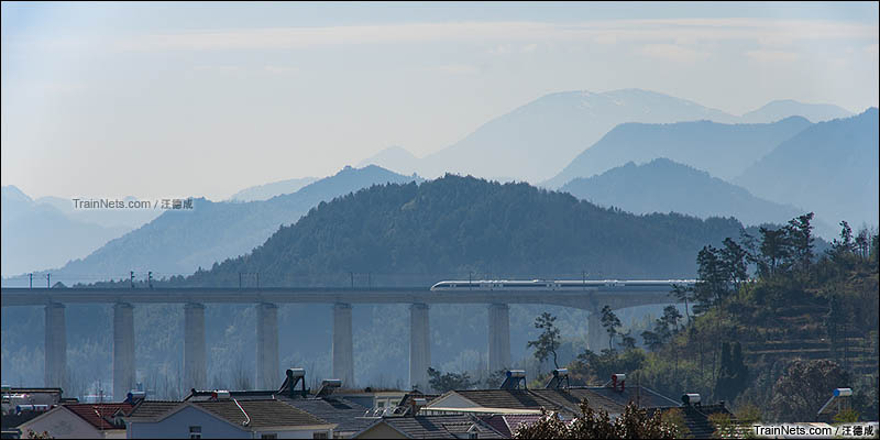 2016年2月9日。安徽旌德。合福高铁,一列CRH380B动车组下行通过旌德站,穿越在崇山峻岭之中。(图/汪德成)