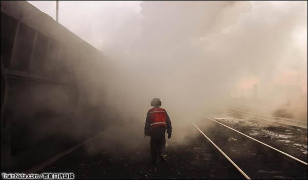 新疆哈密,三道岭煤矿东剥离站。清晨几组蒸爷在东剥离站停妥,师傅开始一一检查全列的情况,穿越蒸汽的水雾,留下远去的背影。(图/西直门折返段)