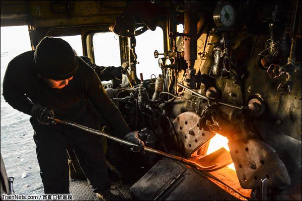 新疆哈密,三道岭矿区。南站。正在给机车填煤的阿里木大车,师傅说这是开蒸汽最累的一项工作。(图/西直门折返段)