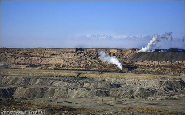 新疆哈密,三道岭露天矿。正在矿坑中行驶的蒸汽机车与煤炭自燃形成的烟雾。由于露天矿开采区地表附近蕴含大量的煤炭,且含硫量较高,常常会发生自燃的现象。由此矿山上散落着大量的冒烟点,发出刺鼻的味道。为避免煤炭自燃引起生产事故及次生灾害,三道岭煤矿还曾有一支灭火队,常年驻扎矿坑边,以消除隐患。(图/西直门折返段)