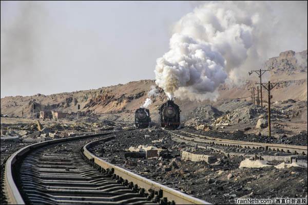 新疆哈密,三道岭露天矿。右侧的列车沿上行线驶出矿坑,而另一侧的机车即将启动,将空车底送入八二站等待装车。图中足以见得坑下线路质量的不堪。(图/西直门折返段)