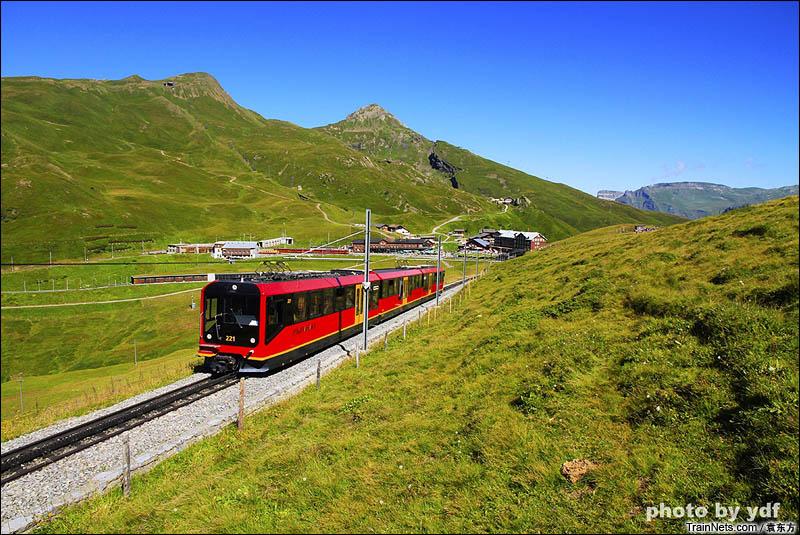 2016年8月14日。瑞士。少女峰铁路,行驶在高山草甸中的红色列车。远处的车站是小沙依德隘口站。(图/袁东方)