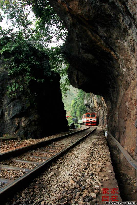"""2012年3月。列车即将通过滇越铁路经典地段:老虎嘴。老虎嘴因为其修建时开凿的明槽酷似一只老虎张开大口,咬向列车。而长龙般的列车毫无畏惧,缓慢而行。在当地又有""""龙虎斗""""之说。(图/家在蒙自)"""