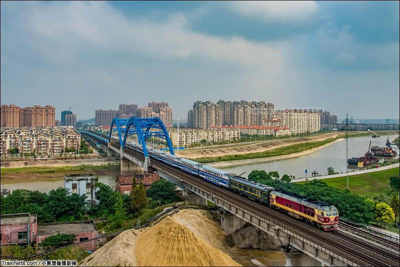 2016年10月8日。阴郁的天空短暂放晴,国庆增开的郑州至杭州临客K4651次列车从高楼群中驶来,通过芜湖青弋江大桥,往宣城方向驶去。好看的S25K双层车底与壮观的大桥构成一道亮丽的风景。这是9月调图停运郑杭双层列车后双层列车再次驶过这座大桥。(图/小黑想做摄影师)