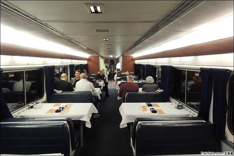 晚间的餐车与用餐的乘客。