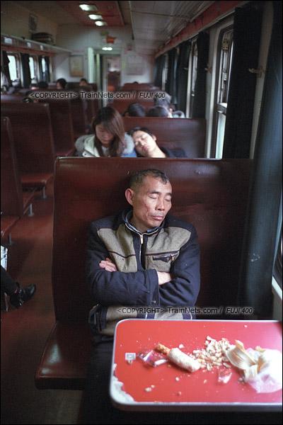 2017年1月1日。5365次长沙至韶山绿皮车,一名乘客在车厢里熟睡。这节车厢被包装成红色旅游列车,桌面、天花板都贴满了红纸。(图/火车仔)