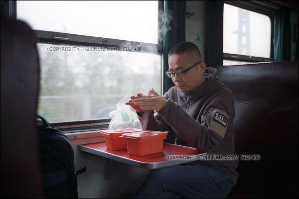 2017年1月1日。5365次长沙至韶山绿皮车,列车正在开往湘潭。一位旅客刚点起了自热米饭,由于天气寒冷,他把双手靠在蒸汽上取暖。(图/火车仔)