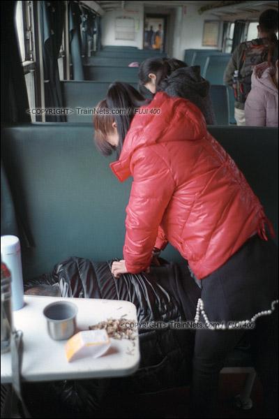 2017年1月1日。5365次长沙至韶山绿皮车,一位女士帮同伴按摩腰部。(图/火车仔)