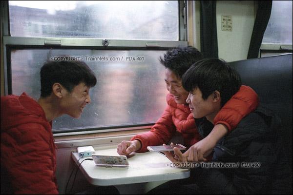 2017年1月1日。5365次长沙至韶山绿皮车,三名前往株洲的年轻人与手机另一头的朋友聊天。(图/火车仔)