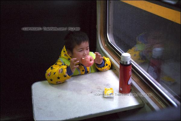 2017年1月1日。5365次长沙至韶山绿皮车,一名孩子调皮地玩着手上的苹果。(图/火车仔)