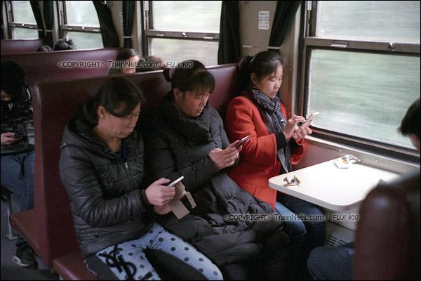 2017年1月1日。5365次长沙至韶山绿皮车,三位乘客拍了窗外风景后齐齐低头发朋友圈。(图/火车仔)