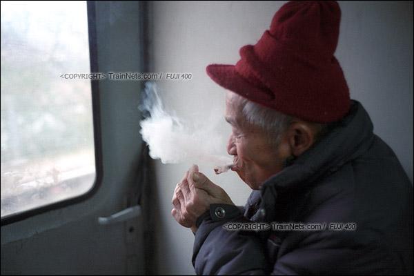 2017年1月1日。5365次长沙至韶山绿皮车,一位老人制作好了手工卷烟后开始吞云吐雾。(图/火车仔)