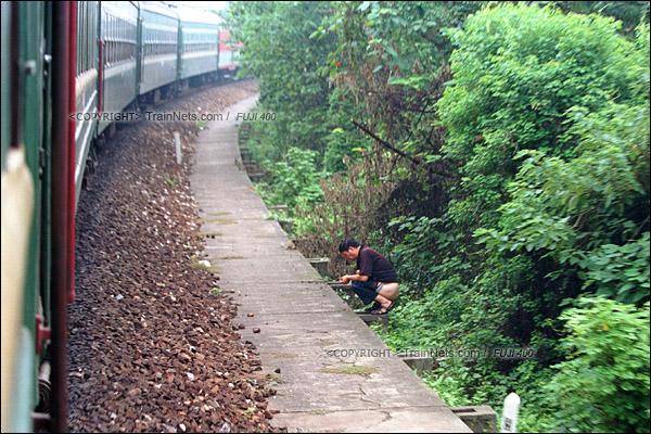 2012年8月。长沙至韶山的5365次绿皮车。列车下了湘江大桥后,偶遇路边一位大便的市民。(D4404/火车仔)