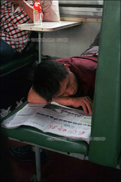 2012年8月25日。 京广线。长沙至韶山的5365次绿皮车。一位趴在椅子上看报纸的乘客睡着了。(D4618/火车仔)